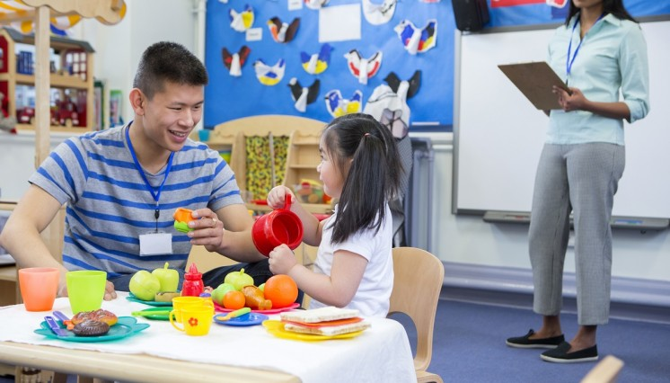 An early childhood teacher plays with a child while a supervisor observes.