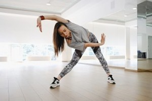 A female hip-hop dancer twists her body in a dance studio