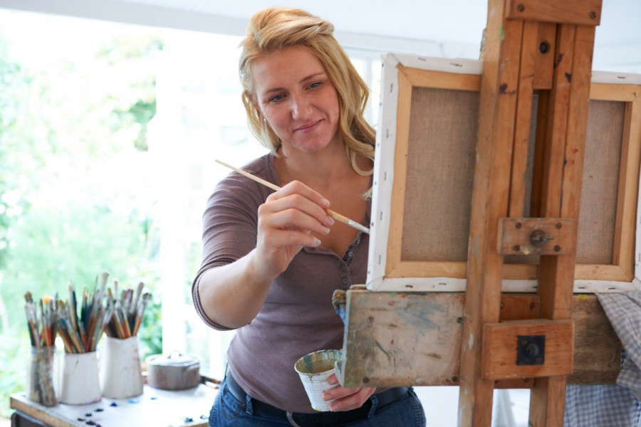 An artist paints a picture in her studio